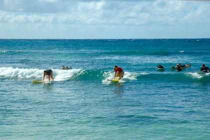 Students surfing at Kiahuna Plantation in Poipu